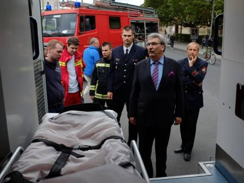 Veranstaltung auf der Straße vor dem Abgeordnetenhaus. Personen in Uniformen (Rettungskräfte, Feuerwehr) erklären Ralf Wieland etwas.
