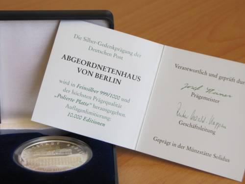 Silbermünze mit Prägung des Abgeordnetenhauses, Karte mit Text zur Herkunft der Münze.