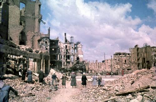 Alte Aufnahme von Berlin nach dem Krieg. Die Häuser sind zerbombt und einige Frauen bilden eine Kette, um Trümmer zu entfernen.