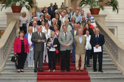 Gruppenfoto mit Ralf Wieland und vielen älteren Personen auf der Treppe des Abgeordnetenhaus.
