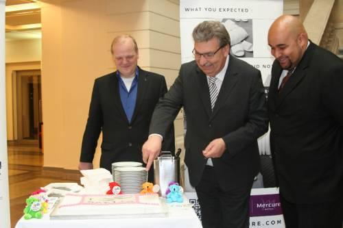 Ralf Wieland schneidet eine Torte an. Neben ihm stehen zwei weitere Männer.