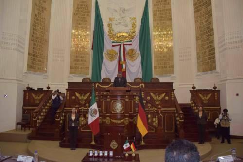 Ralf Wieland steht an einem Rednerpult in Mexiko City. Das Rednerpult ist eine Holzplattform mit Treppen und goldenen Intarsien. Im Hintergrund hängen mexikanische Flaggen. Im Vordergrund die deutsche und mexikanische Flagge.