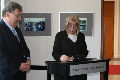 Eine Frau steht an einem Rednerpult und unterschreibt etwas. Ralf Wieland steht neben ihr und guckt zu.