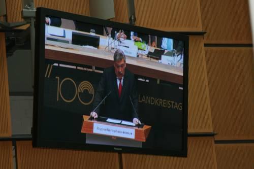 """Foto eines Monitors im Plenarsaal des Abgeordnetenhaus. Man sieht Ralf Wieland am Rednerpult. Hinter ihm ein Plakat: """"100 Landkreistag"""""""