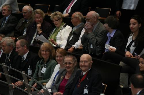 Besucher sitzen auf der Besuchertribüne im Plenarsaal des Abgeordnetenhaus. Einige schauen lächelnd in die Kamera.