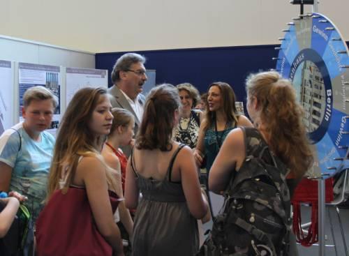 Kinder, Jugendliche und junge Frauen stehen um Ralf Wieland herum. Neben ihnen steht eine Drehscheibe vom Abgeordnetenhaus für ein Gewinn.