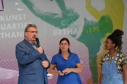 Ralf Wieland steht mit zwei jungen Frauen auf einer Bühne und spricht in ein Mikrofon.