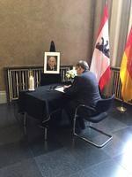 Ralf Wieland sitzt an einem Schreibtisch mit einem schwarzen Tuch und schreibt in ein Kondolenzbuch.