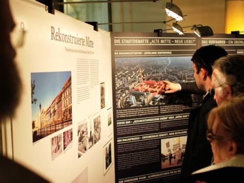 Menschen betrachten eine Ausstellung zur Berliner Mitte.