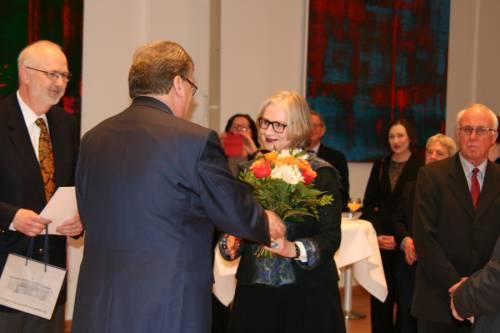 Eine Veranstaltung im Festsaal des Abgeordnetenhaus Berlin. Ralf Wieland übergibt einer Frau einen Blumenstrauß.