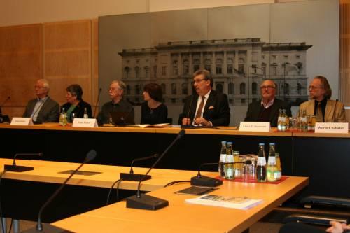 Männer und Frauen sitzen in einer Pressekonferenz an Mikrofonen.