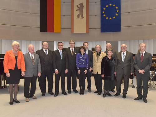Gruppenfoto mit Männern und Frauen im Plenarsaal.