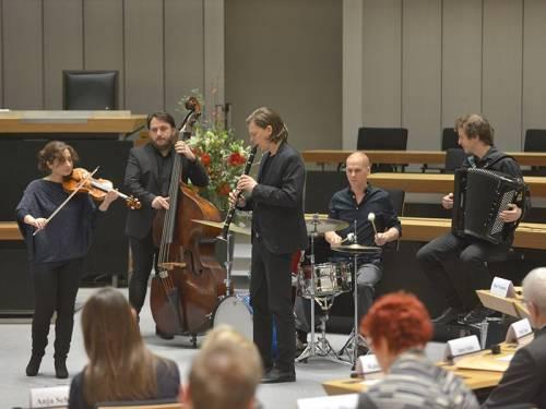 Musiker spielen im Plenarsaal. Darunter eine Geige, ein Contrabass, eine Fagott, ein Schlagzeug und ein Akkordeon.