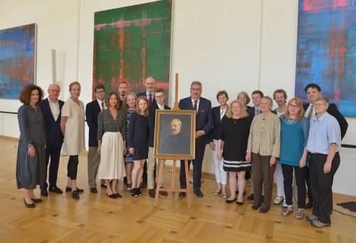 Gruppenfoto im Festsaal des Abgeordnetenhaus Berlin. Viele Menschen stehen um ein Gemälde auf einem Stativ. Das Gemälde zeigt einen alten Mann.
