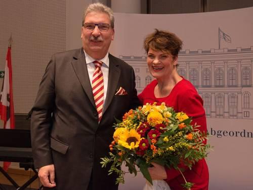 Ralf Wieland hat einer Frau einen großen Blumenstrauß überreicht. Beide lachen in die Kamera.
