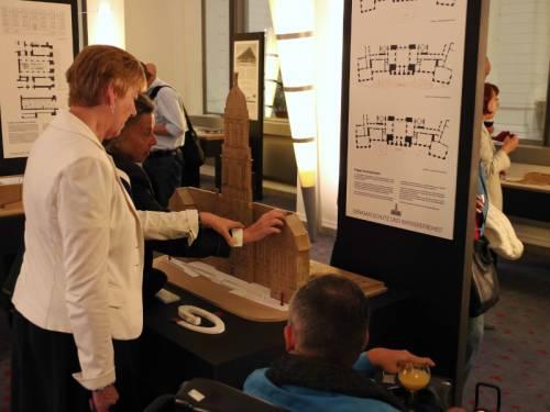 Ein Ausstellungsraum mit Besuchern. Ein Besucher ertastet ein Modell eines Gebäudes.