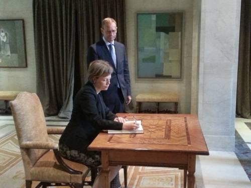Eine Frau sitzt an einem holzernen Schreibtisch und schreibt in ein Buch. Ein Mann steht neben ihr und schaut auf sie.