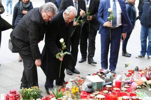 Ralf Wieland und andere legen Blumen auf eine Gedenkstelle mit vielen weiteren Blumen und Kerzen.