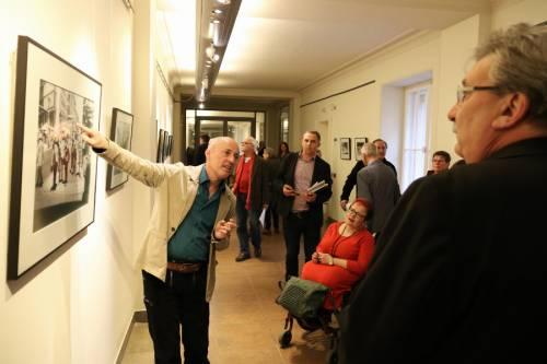 Ein Mann erklärt ein Bild für verschiedene Besucherinnen und Besucher einer Ausstellungseröffnung.