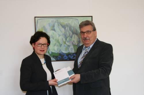 Ralf Wieland nimmt von einer Frau zwei gedruckte Broschüren entgegen. Hinter ihnen hängt ein buntes Bild.