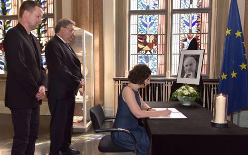 Eine Frau sitzt an einem Tisch mit einem schwarzen Tuch und trägt sich in ein Kondolenzbuch ein. Zwei Männer stehen hinter ihr.