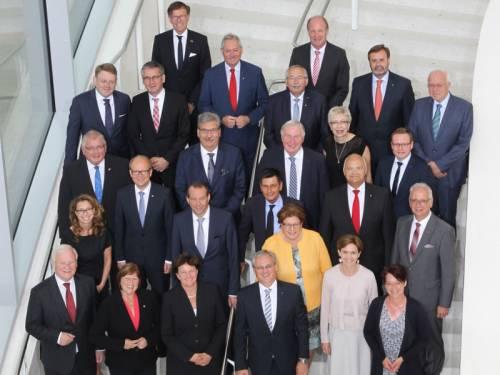 Gruppenfoto von Männern und Frauen, die auf einer Treppe stehen und lächelnd nach oben schauen.