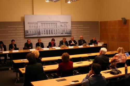 Männer und Frauen sitzen in einer Pressekonferenz an Mikrofonen. Andere hören ihnen zu und stellen Fragen.