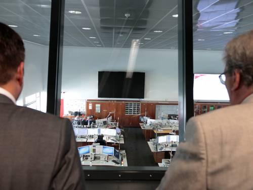 Zwei Männer blicken durch große Fensterscheiben in die Leitstelle der Berliner Feuerwehr. Dort sitzen Menschen an Schreibtischen.