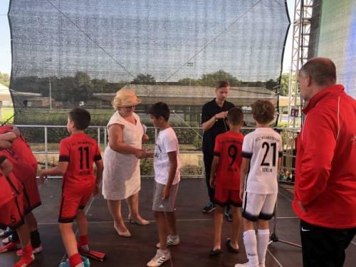 Die Vizepräsidentin des Abgeordnetenhaus gratuliert Jungs, die Fußballtrikots tragen.