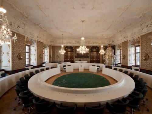 Innenaufnahme eines barocken Saales mit kreisrund angeordneten Tischen und Sitzen in zwei Reihen.