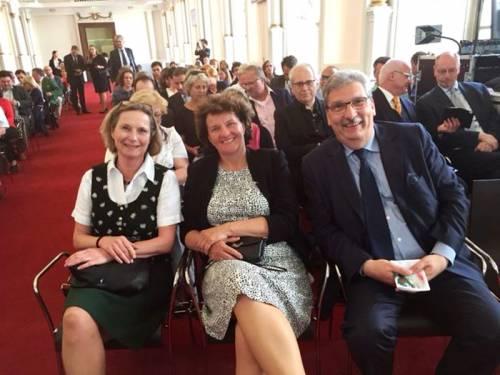 Ralf Wieland sitzt mit zwei Frauen in der ersten Reihe. Alle lachen in die Kamera. Im Hintergrund sieht man weitere Menschen auf Stuhlreihen sitzen.