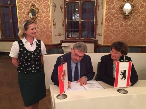 Ralf Wieland trägt sich in das Goldene Buch ein. Auf seiner rechten Seite steht eine Frau. An seiner linken Seite sitzt eine Frau neben ihm.