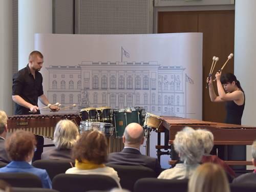 Zwei Musiker mit Xylophonen machen Musik im Festsaal. Man sieht Publikum, was ihnen zuhört.