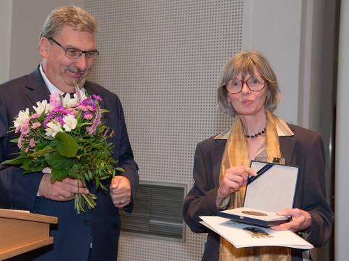 Ralf Wieland übergibt einer Frau einen Blumenstrauß. Sie hält eine Plakette und eine Urkunde in der Hand.