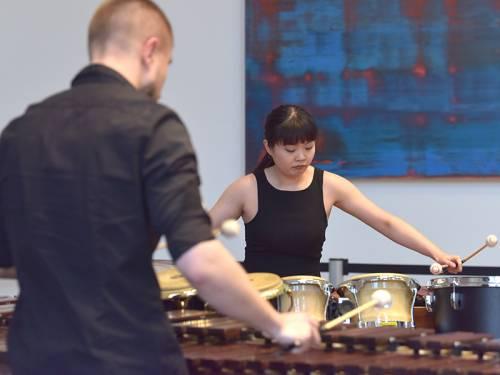 Man sieht den Rücken eines Mannes, er spielt ein großes Xylophon. Vor ihm steht eine asiatische Frau, die trommelt. Sie schaut konzentriert auf ihr Musikinstrument.