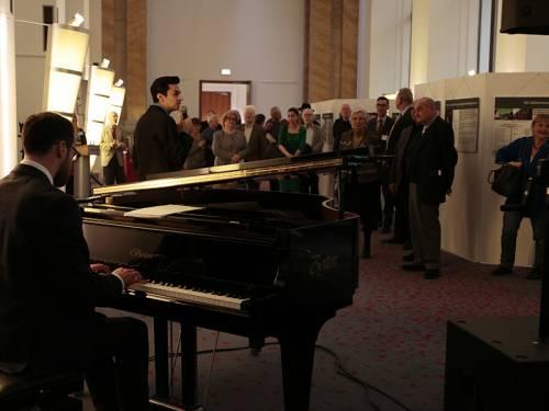 Menschen hören einem Sänger und Klavierspieler zu