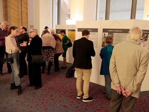 Besucher betrachten eine Ausstellung. Einige Personen unterhalten sich.