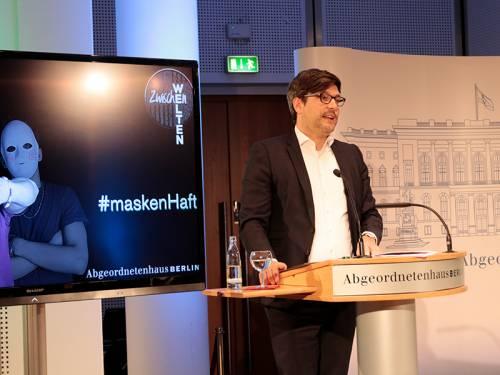 Dr. Dirk Behrendt gibt am Podium ein Grußwort zur Ausstellungseröffnung