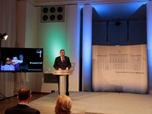 Ralf Wieland spricht an einem Podium und eröffnet eine Ausstellung.