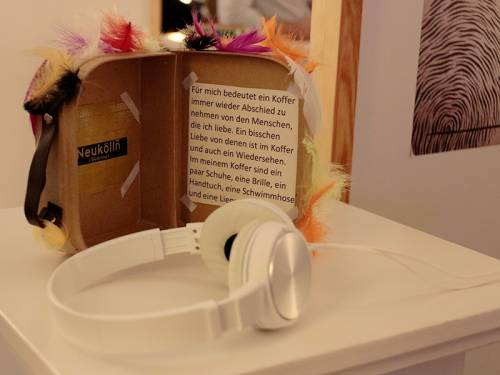 Nahaufnahme eines Werkes in einer Ausstellung. Im Vordergrund liegen Kopfhörer, dahinter ein gebastelter Koffer mit Federn.