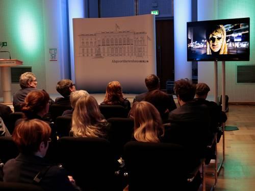 Zuschauer schauen auf einen Fernseher im Rahmen einer Ausstellung.