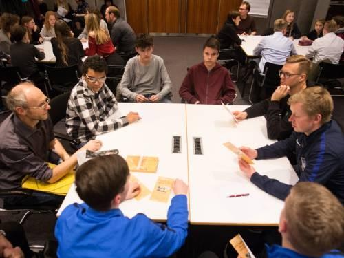 Erwachsene und Jugendliche sitzen an Tischen zusammen.