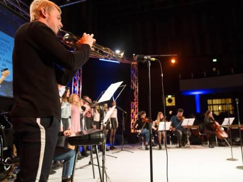 Man sieht wie Kinder und Jugendliche auf einer Bühne musizieren. Im Vordergrund ist ein junger Mann mit einer Trompete.