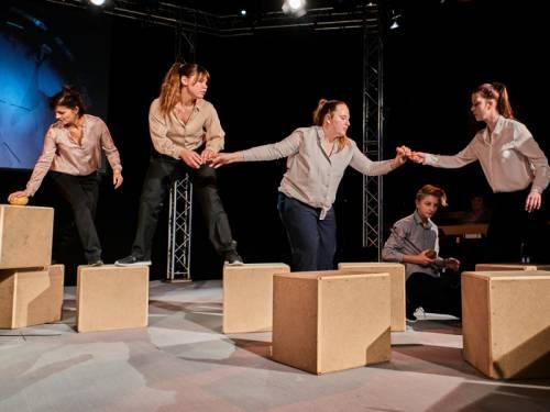 Schüler laufen über Hocker auf einer Bühne, alle tragen dunkle Hosen und helle Hemden und Blusen