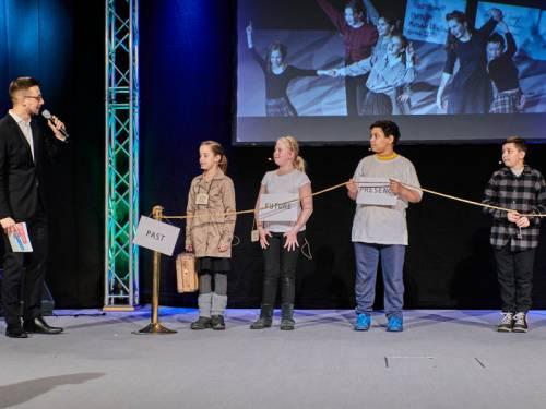 Kinder stehen auf einer Bühne. Ein Moderator spricht mit ihnen.