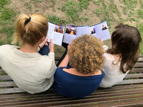 Man sieht aus der Vogelperspektive wie drei junge Frauen sich eine Broschüre anschauen.