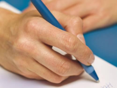 Nahaufnahme mit einer Hand, die etwas mit einem Kugelschreiber schreibt