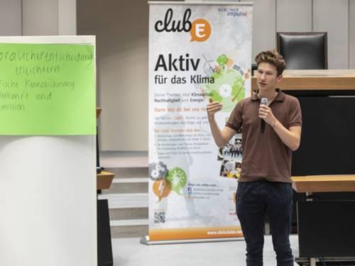 Ein Jugendlicher spricht vor einem Poster in ein Mikrofon