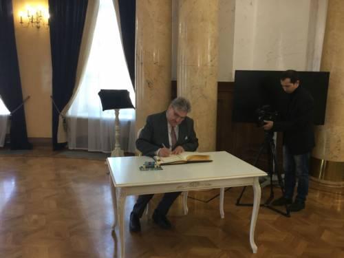 Ralf Wieland trägt sich in das Ehrenbuch ein. Ein Kameramann filmt dies.