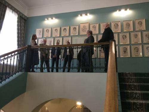 Eine Gruppe von Menschen steht vor einer Wand mit Ehrenbürger Portraits